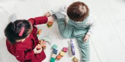 Children learning through play with wooden toy blocks.